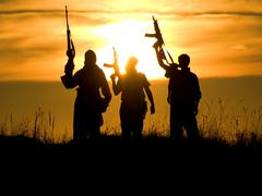Soldiers against a sunset Stock Photos