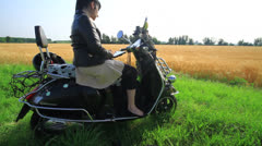 Girl writes on the tablet sitting on his Vespa 1 Stock Footage