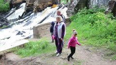 Family with two children walking in forest river - stock footage