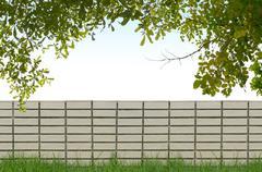 shrubs and brick fence on blue sky background - stock photo