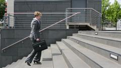 business woman walking upstairs with smartphone - stock footage