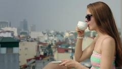 Girl drinks coffee on the roof Stock Footage
