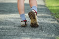 woman walking in the park, sport shoe closeup - stock photo