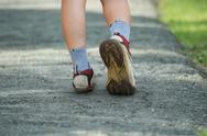 Stock Photo of woman walking in the park, sport shoe closeup