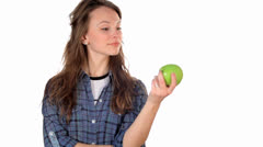 Woman eating a green apple isolated on white Stock Footage