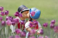 Two kissing dolls in tulip garden. Stock Photos