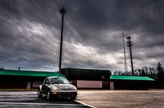 A volkswagen beatle, parked outside an abandoned shopping plaza. Stock Photos