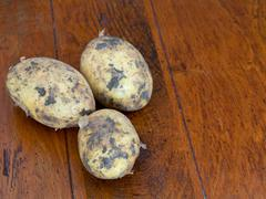 raw potatoes on brown table - stock photo