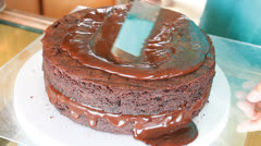 Baker decorated chiffon chocolate cake with chocolate topping Stock Footage