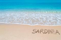 "turquoise foreshore with ""sardinia"" written on it - stock photo"