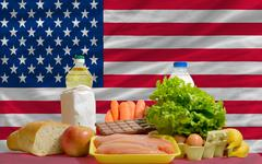 basic food groceries in front of america national flag - stock photo
