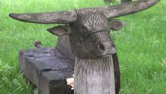 Wooden bench in resort park with cow head sculpture Stock Footage