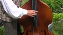 Musician playing with contrabass in summer  fair Stock Footage