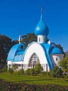 orthodox white church with blue domes in the park area - stock photo