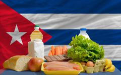 basic food groceries in front of cuba national flag - stock photo