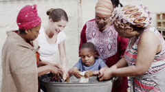 African family and community members work together, washing clothes by hand - stock footage