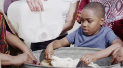 African family and community members work together, washing clothes by hand Stock Footage