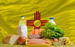 basic food groceries in front of new mexico us state flag - stock photo