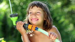 Boy playing with water in the garden Stock Footage