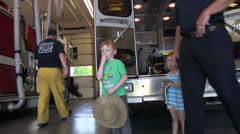 Children visit fire station, fireman Stock Footage