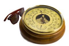 Barometer - aneroid on a white background and black sunglasses Stock Photos