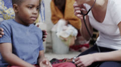 Medical worker from charity organisation lets little boy use her stethoscope - stock footage