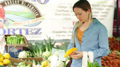 Young Asian Woman Buying Yellow Squash at Farmers Market Stock Footage