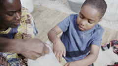 African family working together, measuring out quantities of rice or grain - stock footage