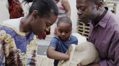 African family working together, measuring out quantities of rice or grain  Stock Footage