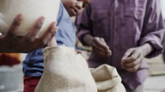 African father and son measuring out cups of rice or grain from a hessian sack Stock Footage