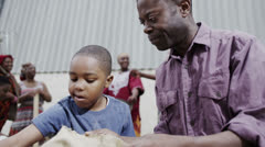 African father and son measuring out cups of rice or grain from a hessian sack - stock footage