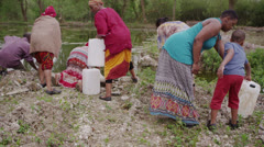 African villagers at river fill containers with as much water as they can carry Stock Footage