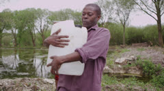African villagers at river fill containers with as much water as they can carry - stock footage