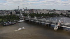 The Hungerford Bridge crosses the River Thames in London Stock Footage