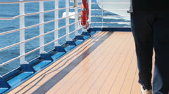 Man walks by on cruise ship deck blue ocean water HD 7831 Stock Footage