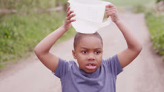 Young African boy travels down a dirt road carrying a container of water - stock footage