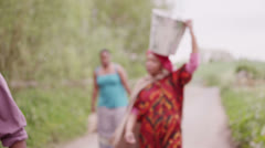 African villagers carry containers of water back to their village Stock Footage