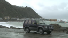 cars pass by washed out sea wall - stock footage