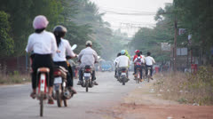 People riding motorcycles and bicycles in early morning Cambodia Stock Footage