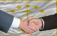 in front of american state flag of rhode island two businessmen handshake aft - stock photo