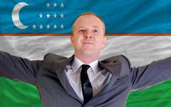 Stock Photo of happy businessman because of profitable investment in uzbekistan standing nea