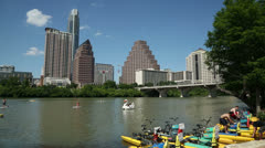 people enjoy water sports on lady bird lake, austin skyline, texas, usa - stock footage