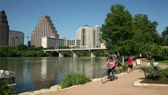 two cyclists ride along the lady bird lake trail, austin - stock footage