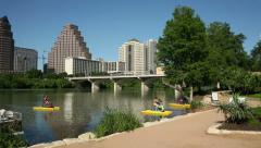 Women enjoy paddling on lady bird lake, austin skyline, texas, usa Stock Footage