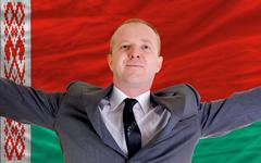 Stock Photo of happy businessman because of profitable investment in belarus standing near f