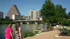 Women walk along the lady bird lake trail with austin skyline in background Stock Footage