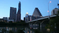 Sunset cruise bat tour boat passes under congress avenue bridge at twilight Stock Footage