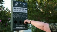 Woman takes dog waste bag from dispenser, austin, usa Stock Footage