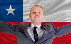 Stock Photo of happy businessman because of profitable investment in chile standing near fla
