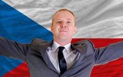 Stock Photo of happy businessman because of profitable investment in czech standing near fla